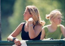 Princess Madeleine stands on the side of and views the horse competition at Stockholm rider's game.