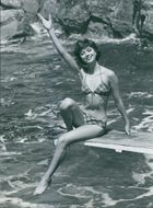 Marie-Hélène Arnaud wearing a swimsuit while sitting on the edge of the diving board.