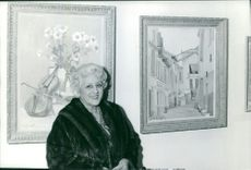 A woman standing beside the paintings.