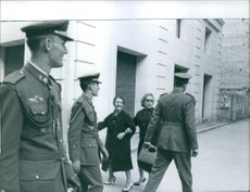 Women spectators catch a glimpse of Don Juan Carlos de Bourbon, King of Spain, and other soldiers walking the streets.