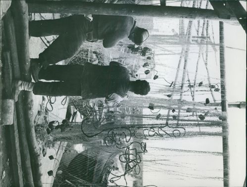 Two fishermen are busy working on a fish net while being photographed.