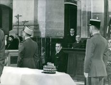 Jacques Chaban-Delmas in a court room with other people.