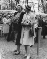 Two women walking with flowers in their hand.
