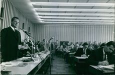 Willy Brandt is speaking while the audience are listening and some of them are taking notes about the conference. 1961