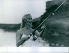 Eliette Mouret holding fishing pole.