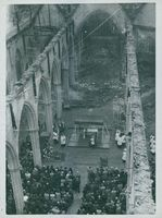 People gathered for a mass inside a church damaged by war. Photo taken in 1942 in England.