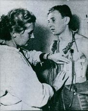 A photo of a woman measuring heartbeat and giving medical treatment to a man standing in front of her.