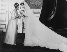 Princess Alexandra with a woman on her wedding, looking at something on her hand.