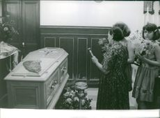 Scene of women using aspergillum to sprinkle holy water to the coffin.  - Jul 1964