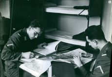 Soldiers plotting the maps and marking some books.