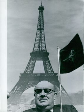 Close up photo of Paul-Henri Spaak, in the background is the Eiffel tower.