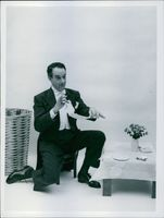 Victor Borge sitting on a small chair by a small table.