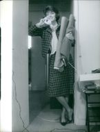 Marie-Hélène Arnaud was standing and holding a phone. 1962