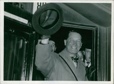 Maurice Chevalier smiling and showing his hat.