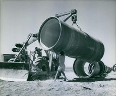 A large round pipe being lifted by crane, man supporting.