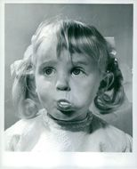 A young child enjoys chewing her bubble gum.