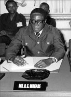 Robert Mugabe sitting on chair with his nameplate in front.