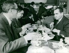 Pierre Mendes France eating with other two men.