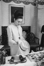Soraya Esfandiary Bakhtiari watching stuff lied on the table holding her hat in her hands.