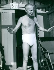 Darryl Francis Zanuck in his trunks while smoking a cigarette.