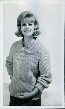 Photograph of a woman standing and smiling.