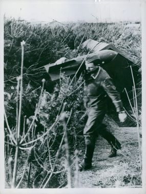 A soldier carrying a big bomb on his shoulders in Berlin.