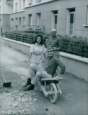 Jacqueline Boyer laughing while pushing a cart while husband is sitting.
