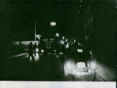 People gathered in street at night. 1972
