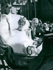 Princess Birgitta and Johann Georg, of Sweden and Hohenzollern, ride the open carriage during their wedding parade. 1961.