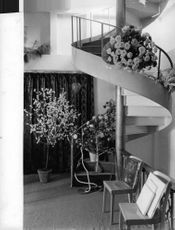 A well-furnished luxurious room with a swirling staircase attached.