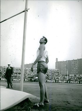 Athlete looking the height of high jump pole.