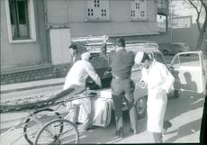 Men putting an injured man into car.
