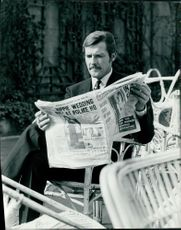 Roger Moore reading newspaper.