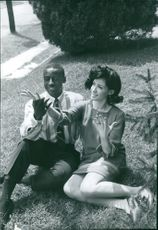 A man and a woman sitting on grass while he looks at her palms.