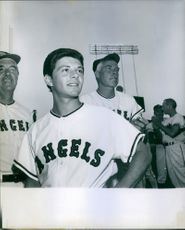 Vintage photo of Frankie Avalon wearing a baseball jersey posing in a baseball field.