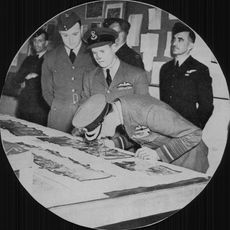 English King George VI is looking at aerial photographs. Behind him is the squad leader Gibson