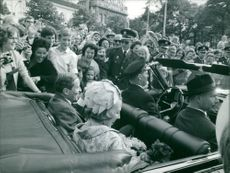 Beatrix and Claus of the Netherlands sitting in car, surrounded by people.