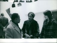 Felix Houphouet-Boigny in a conversation with two women.