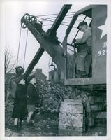 Two English boys chatting with an American soldier operating a steam shovel which is clearing away the rubble.
