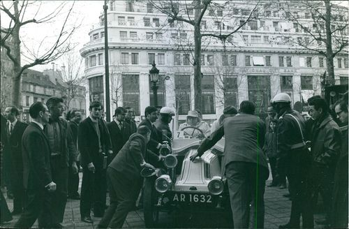 Renault car pushed by the men with other men watching, 1967.