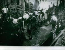 Workers washing ships floor together. 1963
