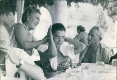 A woman tying Melina Mercouri's hair whilst Jules Dassin is watching them.