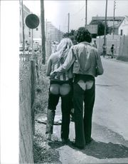 A couple wearing pants that shows off their bottoms. 1972.