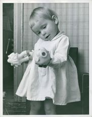 A young girl playing with her broken doll.