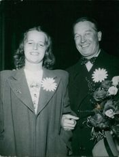 Maurice Chevalier with a woman, smiling.