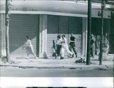 People running together on side walk. 1961