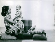 Dewi Sukarno carrying her child.