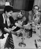 Danny Kaye sitting at table with friends.