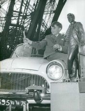 A boy on his suit sitting on a car and holding a mini model of the Eiffel Tower. 1960