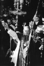Pope Paul VI standing with his arms open.